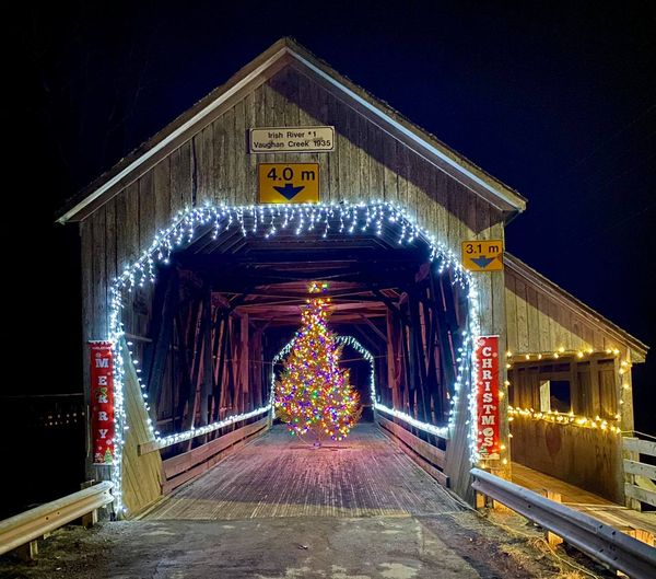 St. Martins, New Brunswick, covered bridge with Christmas tree, lit, at night