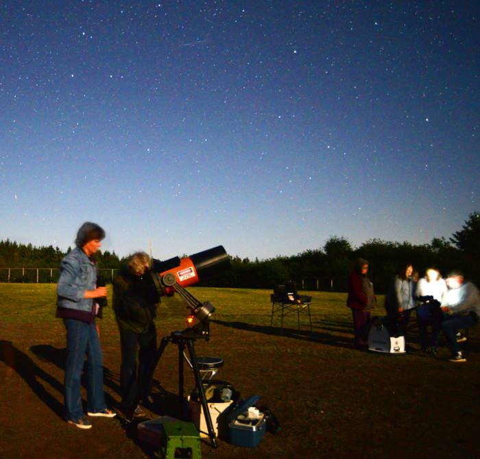 Personnes observant le ciel au télescope la nuit.